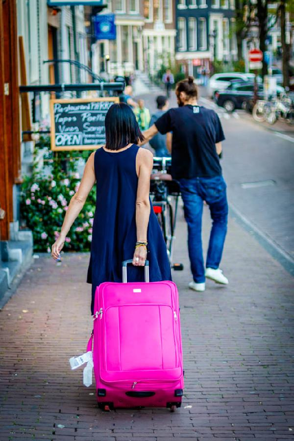 Streets of Amsterdam. Girl with pink suitcase.
